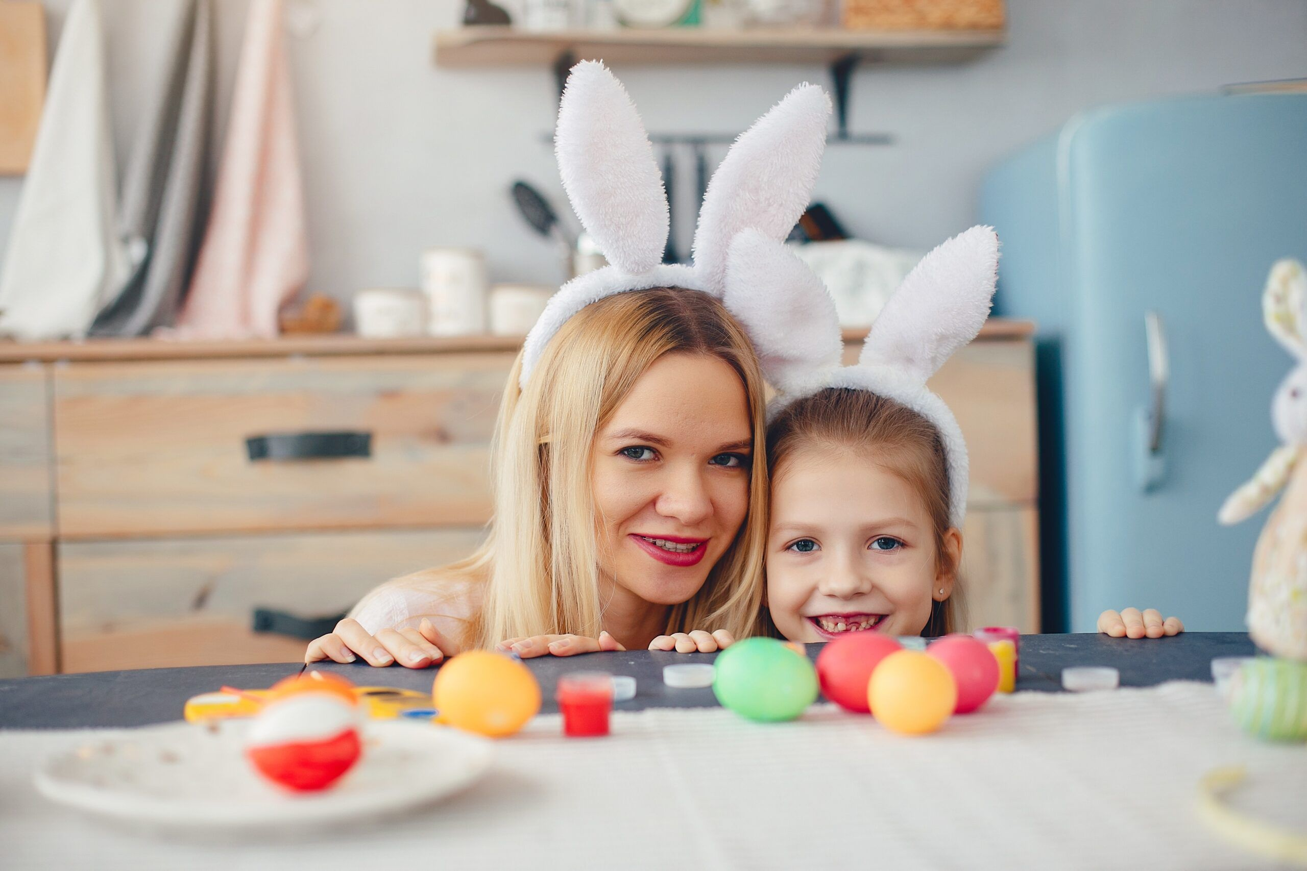 Mother And Daughter Paint Eggs. Family In A Kitchen. Preparing For Easter