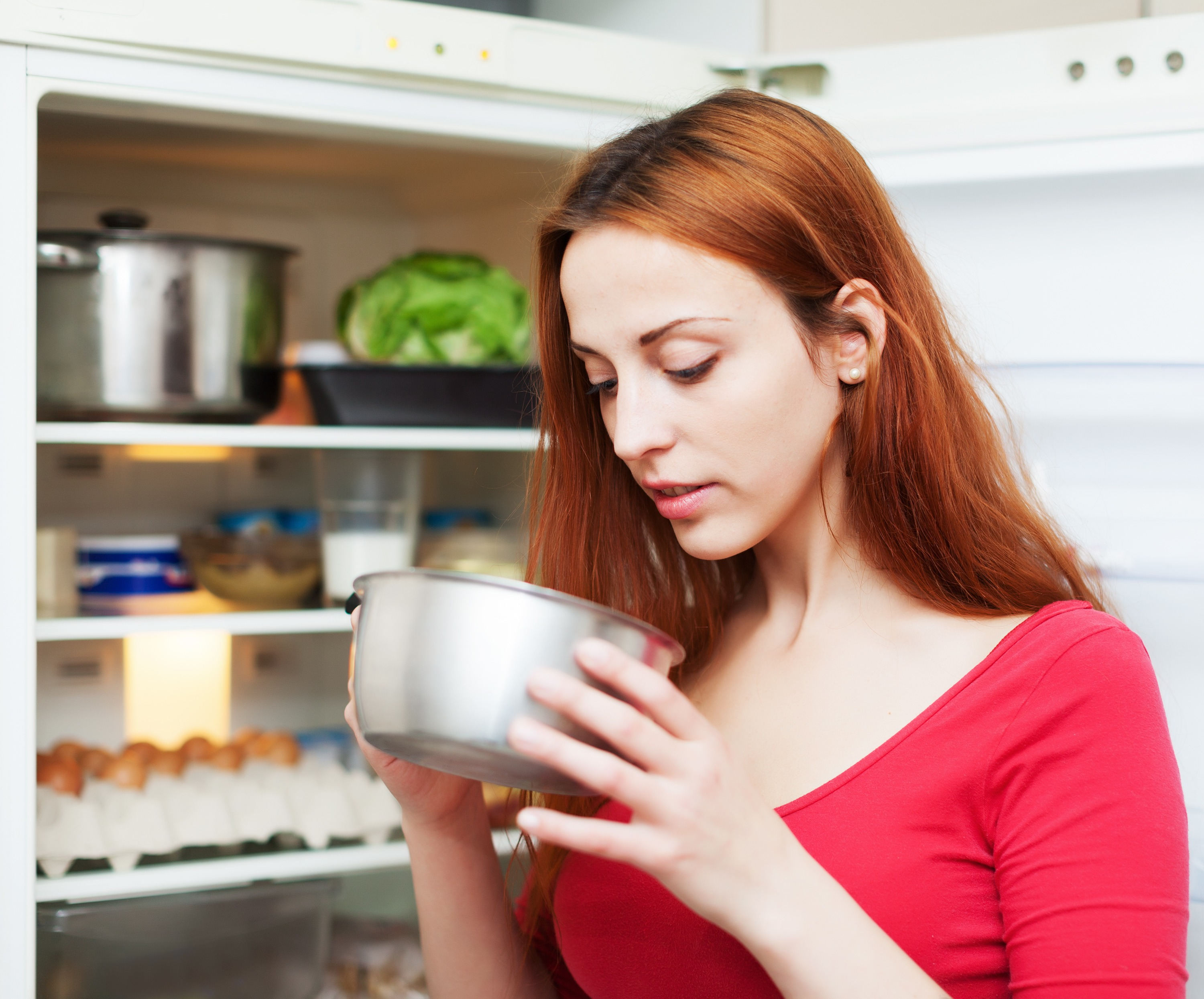 Red-haired Woman Looking For Something In Pan Near Fridge At Home