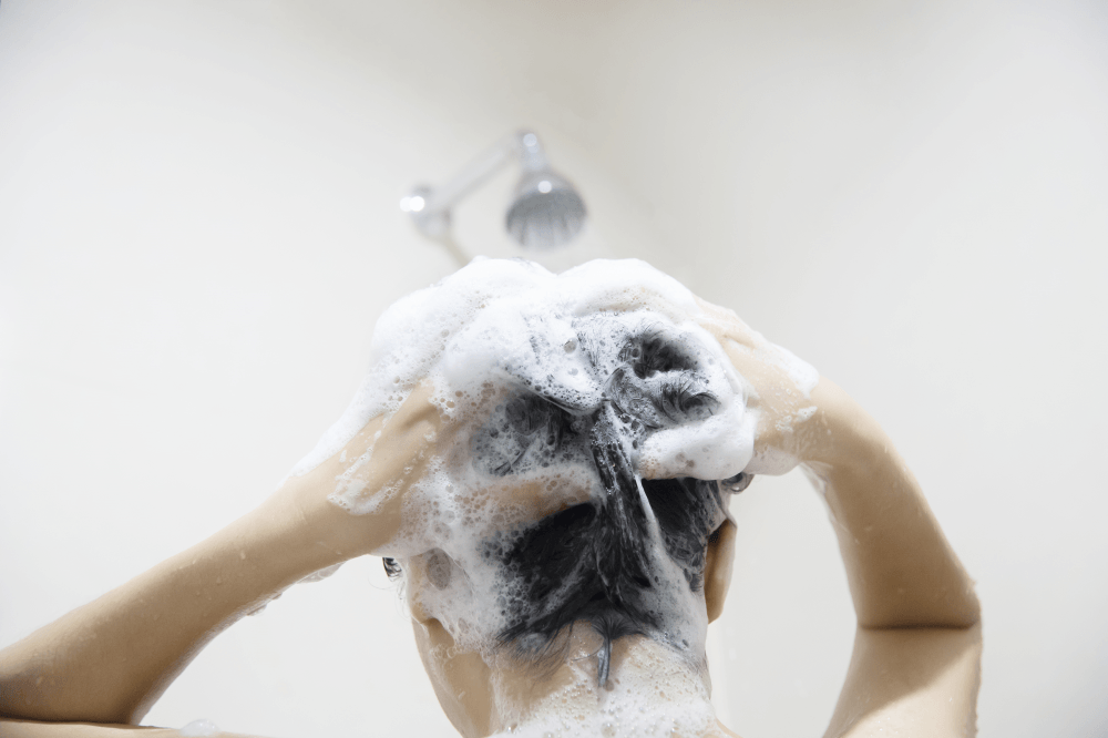 Black haired woman washing her hair