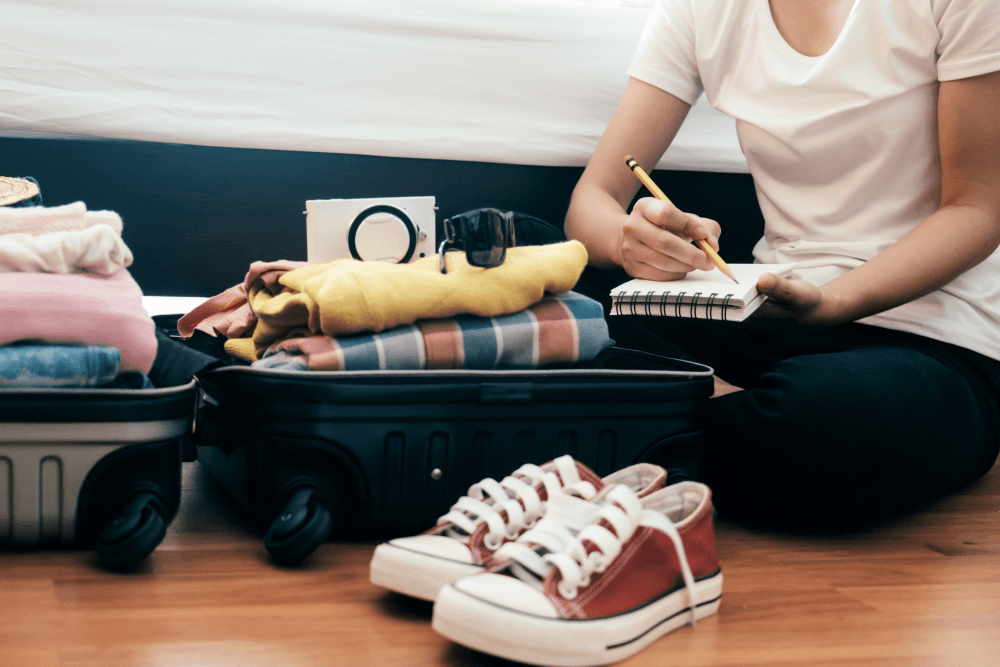 Woman Preparing Luggage For A Trip Using A List