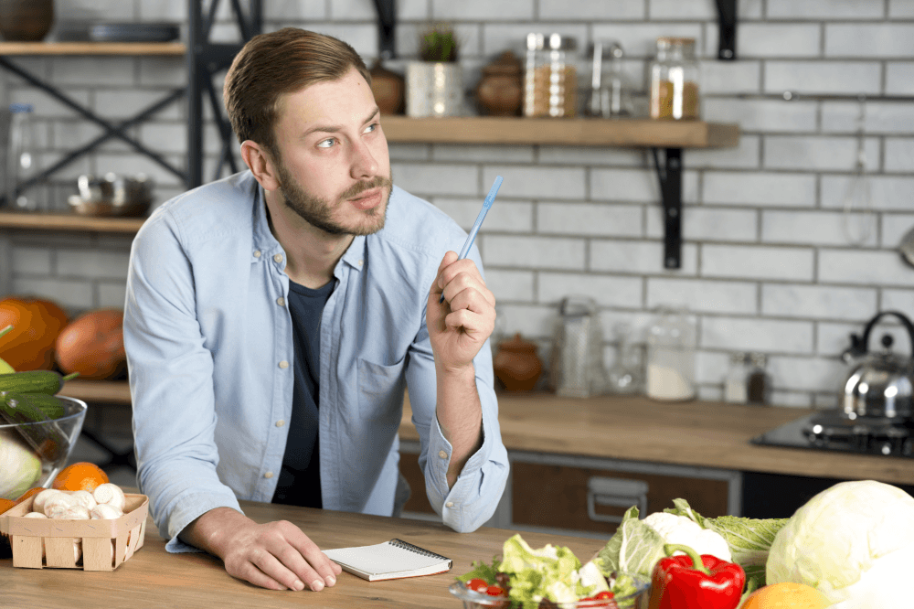 Young man thinking what to write on shopping list