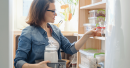 Middle Aged Woman Selecting Ingredients From Kitchen Cabinet