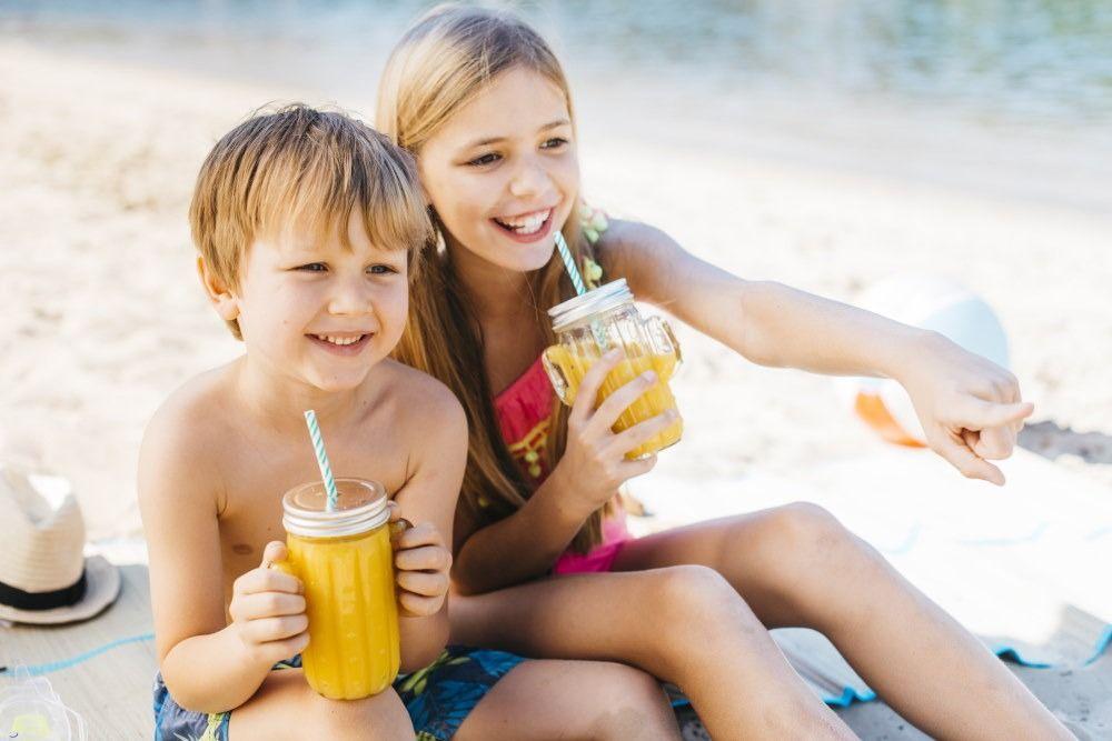 Children drinking juice at the beach