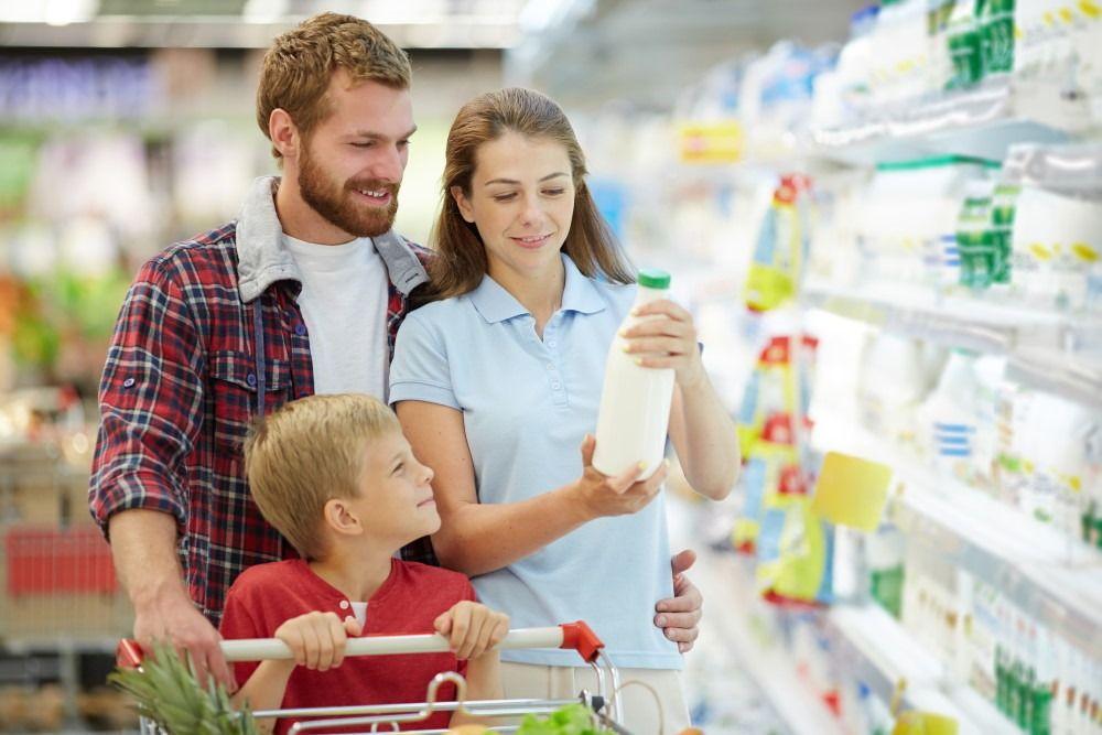 Happy family at super market buying milk