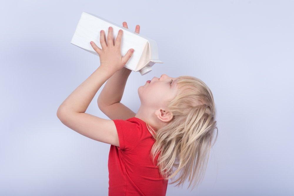 Little boy drinking milk from carton