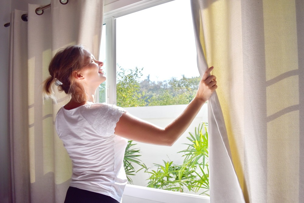 oung woman opening windows